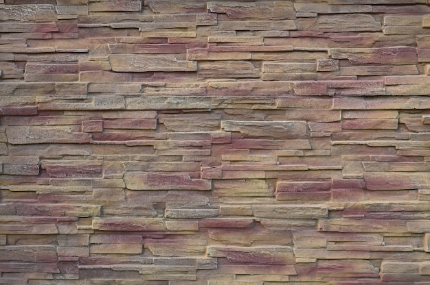 Rood-geel gescheurde bakstenen muur
