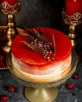 Rood geglazuurde cake met granaatappel en caramel driehoeken