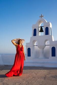 Rood geklede vrouw in oia, santorini, griekenland.