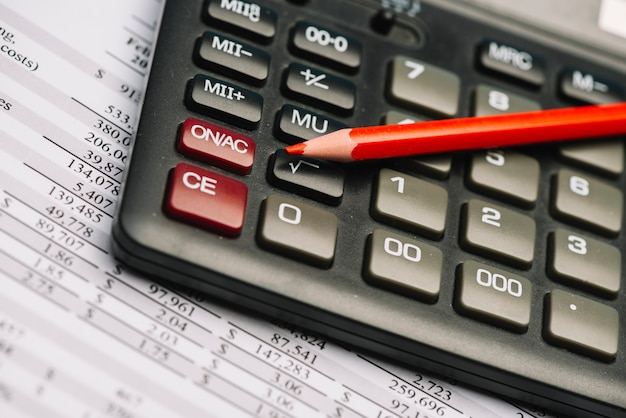 Rood gekleurd potlood op calculator over het financiële rapport