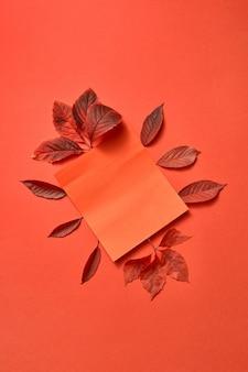 Rood gekleurde herfstdruivenbladeren en papieren kaart op een koraalachtergrond met zachte schaduwen, kopieerruimte. plat leggen. groet samenstelling.