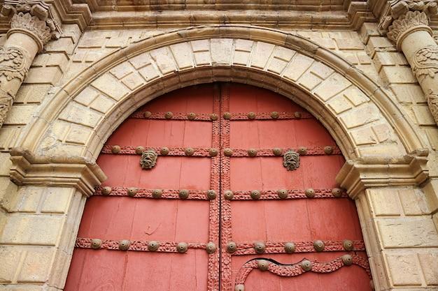 Rood gekleurde houten deur van de basiliek van san francisco in la paz, bolivia