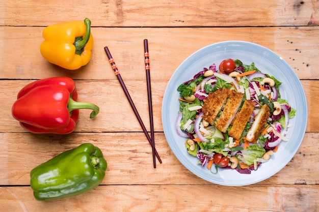 Rood; gele en groene paprika met stokjes en thaise salade op het bureau