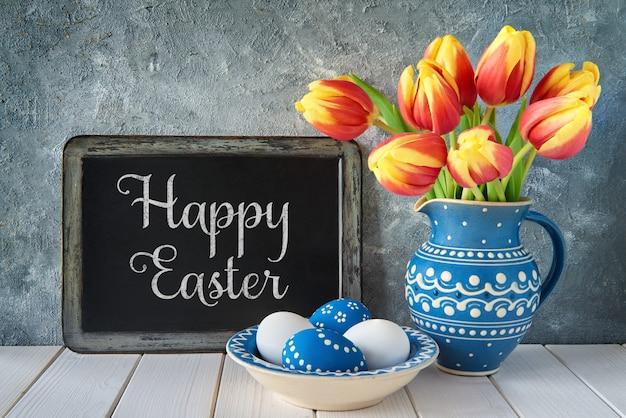 Rood-gele tulpen in blauwe ceramische waterkruik met paaseieren en een bord op grijs, tekst