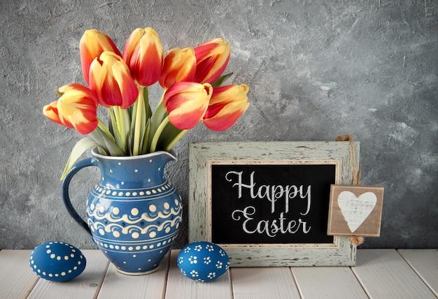 Rood-gele tulpen in blauwe ceramische waterkruik met paaseieren en een bord op grijze achtergrond, tekst