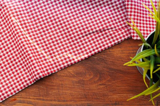 Rood geruit servet of tafellaken op houten tafel, kopie ruimte