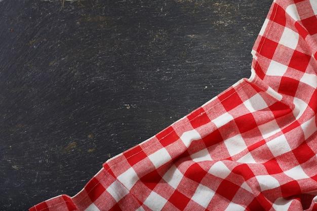 Rood geruit tafelkleed op donkere tafel, bovenaanzicht met kopie ruimte