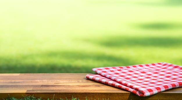 Rood geruit tafelkleed op hout met groene binnenplaats achtergrond wazig