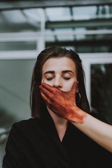 Rood geschilderde hand voor mond van een vrouw met gesloten ogen. concept van stilte