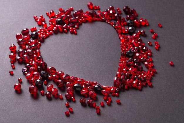 Rood geslepen glaskralen op zwarte achtergrond, hartvormig