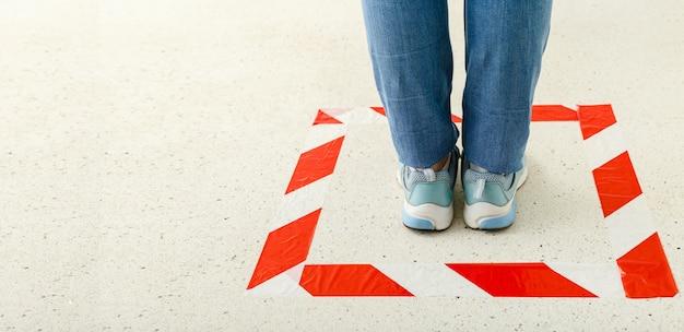 Rood gestreept lijnteken om sociale afstand te houden. vrouw achter een waarschuwingslijn tijdens covid 19 coronavirus quarantaine. veilig winkelen, sociaal afstandsconcept. webbanner met kopie ruimte