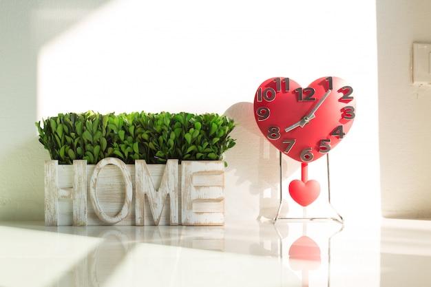 Rood gevormd hart van decoratieve klok en thuis alfabetalfabet