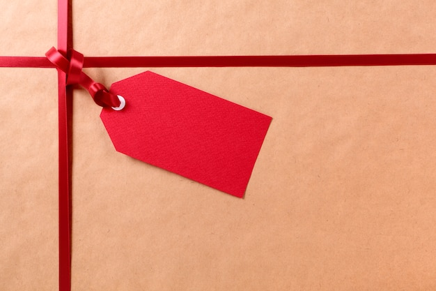 Rood giftlabel en lint, bruine pakket verpakkend document achtergrond, exemplaarruimte.