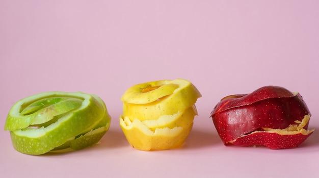 Rood groen gele appel schillen op roze achtergrond als een symbool van recycling circuleren economie