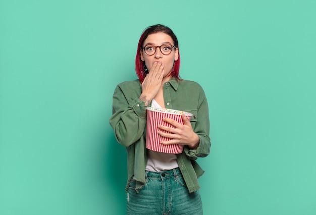 Rood haar coole vrouw met popcorns en een tv-afstandsbediening