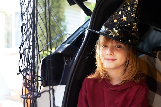 Rood haar van het meisje met een heksenhoed die de autokoffer van halloween viert