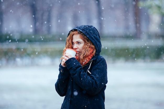 Rood haar vrouw met een koud drankje in de winter