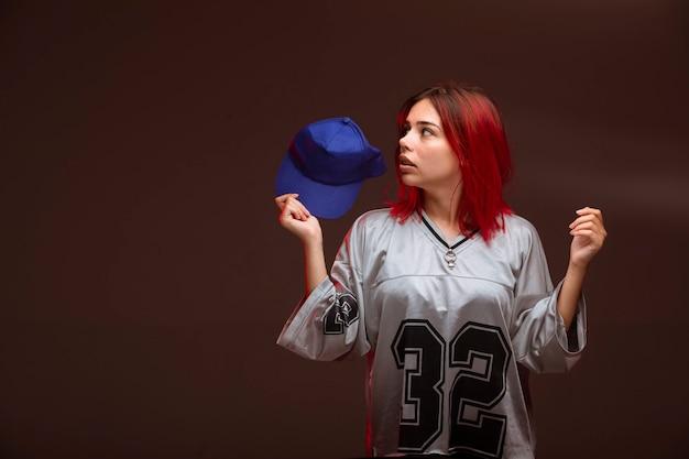 Rood haarmeisje in sportoutfits ziet er bang uit.