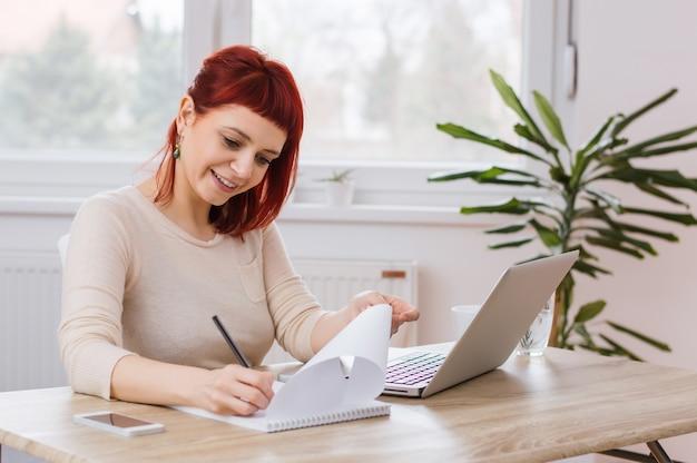 Rood haired meisje dat iets op een stuk van document schrijft