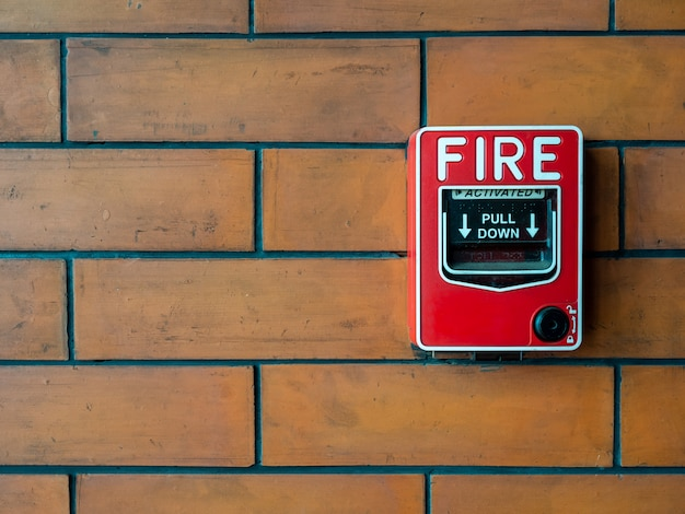 Rood handbrandalarm op bakstenen muur