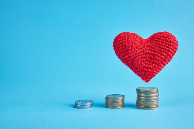 Rood hart dat onder muntstukstapels over blauw vliegt. kopieer ruimte. geldmunten trappen naar liefde en romantiek concept. hou van geld concept