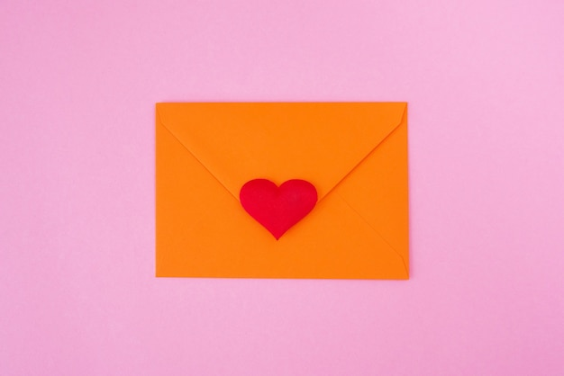 Rood hart en envelop op roze achtergrond