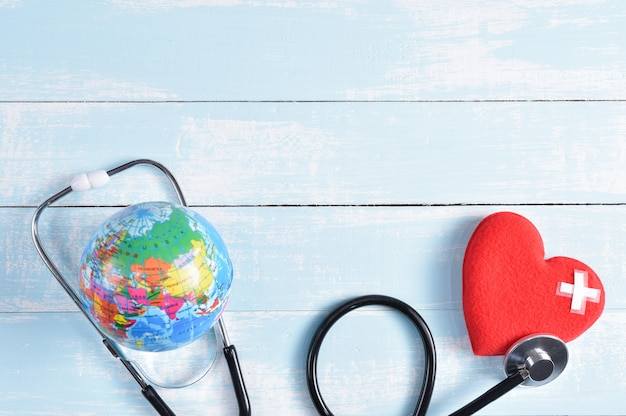 Rood hart en globe op blauwe en witte pastel houten achtergrond.