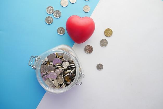 Rood hart en munten in een pot op gekleurde achtergrond