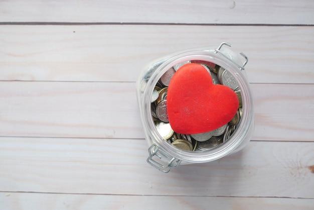 Rood hart en munten in een pot op houten achtergrond