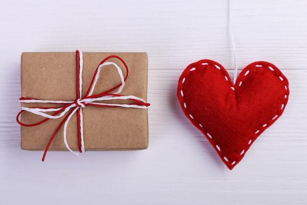 Rood hart gemaakt van vilt en handgemaakt, op een witte houten tafel