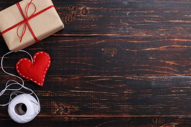Rood hart gemaakt van vilt handgemaakt, cadeau, naast de draad en een naald, op een houten tafel. vrouwendag concept, kopie ruimte.