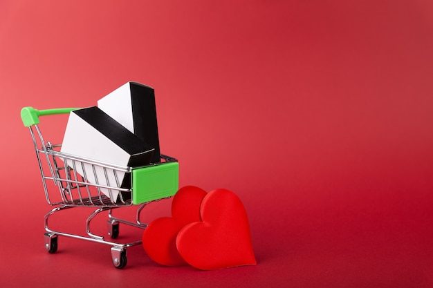 Rood hart, geschenkdoos met rood lint in mini kruidenierswinkelwagentje op gekleurde achtergrond