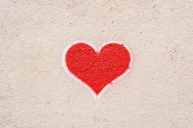 Rood hart geschilderd op een muur, boodschap van liefde.