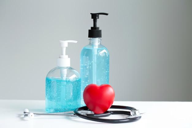 Rood hart, handdesinfecterend gel, stethoscoop op witte lijst. , stop met het verspreiden van het coronavirus, het concept van de gezondheidszorg.