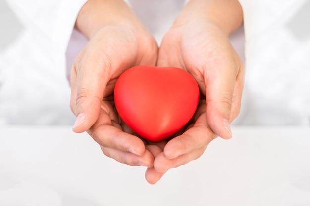 Rood hart in de hand gezondheidszorgconcept voor wereldgezondheidsdag of valentine-dag.