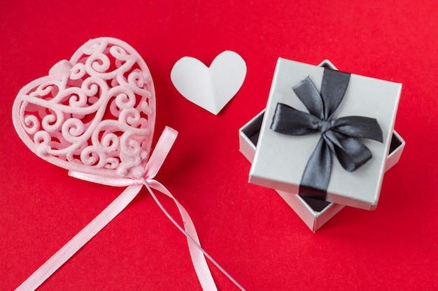 Rood hart in geschenkdoos op rode achtergrond