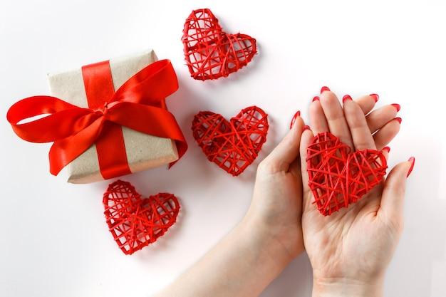 Rood hart in handen op een witte achtergrond. een rood hart in handen op een witte achtergrond. valentijnsdag geschenk