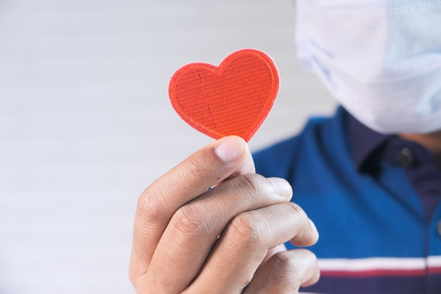 Rood hart in handen, schenkt of liefdadigheidsconcept.