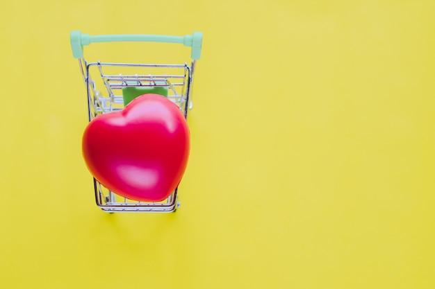 Rood hart in winkelwagen op gele vintage achtergrond.