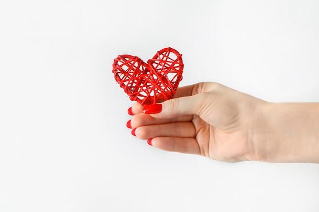 Rood hart in zijn uitgestrekte hand op een witte achtergrond