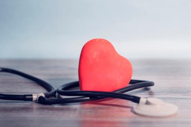 Rood hart liggend op een houten tafel, zorgvuldig verstrengeld met een statoscoop. concept van zorg, hulp, medicijnen.