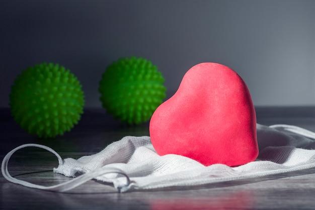 Rood hart ligt op het beschermende masker. in de schaduw twee groene ballen met spikes die het coronavirus symboliseren.