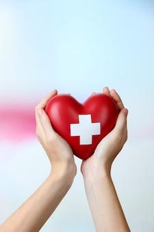 Rood hart met dwarsteken in vrouwelijke hand, close-up, op lichte oppervlakte
