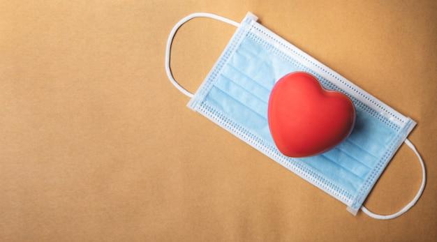 Rood hart met een blauw beschermend chirurgisch masker op bruin papier