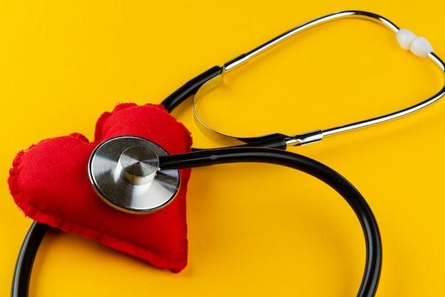 Rood hart met een stethoscoop op gele muur. cardioloog concept.