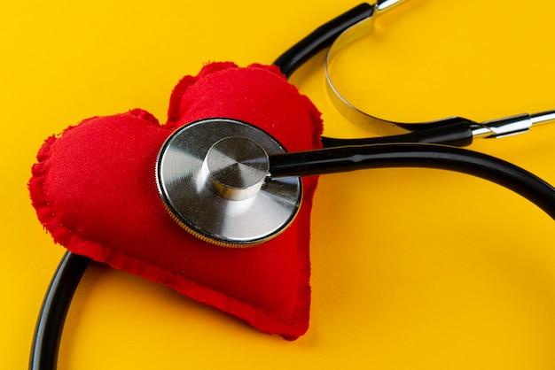 Rood hart met een stethoscoop op gele muur. gezondheid concept.