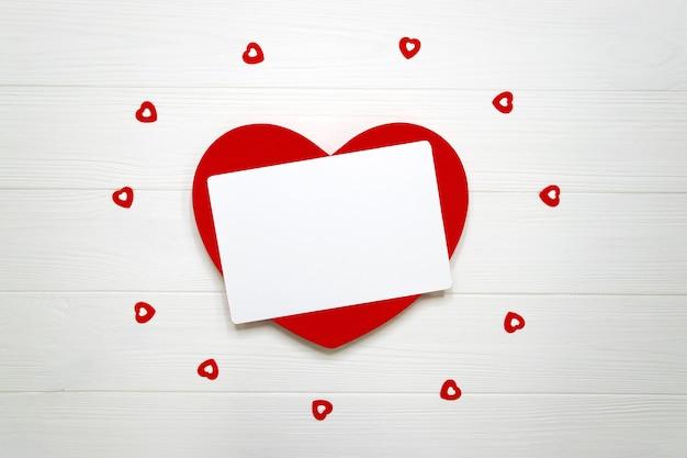 Rood hart met lege kaart, vele kleine harten op wit houten bord. valentijnsdag plat leggen