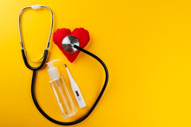 Rood hart met stethoscoop, alcohol gel en thermometer op gele muur. concept van sociaal isolement.