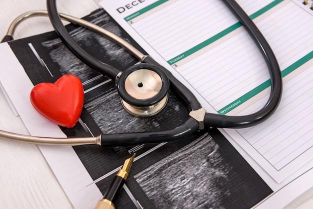 Rood hart met stethoscoop en analyseresultaten op tafel