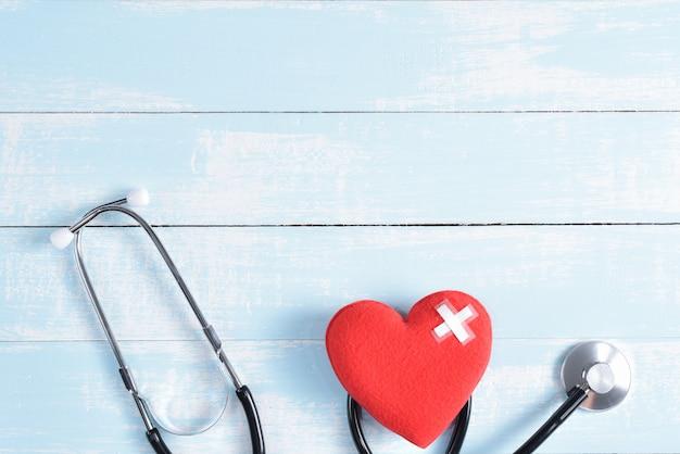 Rood hart met stethoscoop op blauwe en witte pastel houten achtergrond.